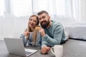 Fotografie Glückliches Paar mit Laptop am Boden liegend und Online-shopping