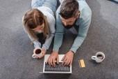Paar liegt mit Getränken auf dem Boden und kauft online ein
