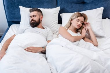 bearded man and attractive girl sleeping in white bed