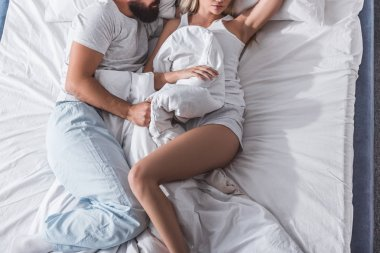 cropped view of young couple lying in white bed and sleeping in morning