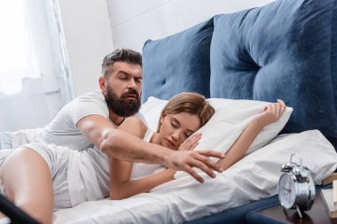 sleepy bearded man waking up and turning off vintage alarm clock on nightstand while pretty girl sleeping in white pillows