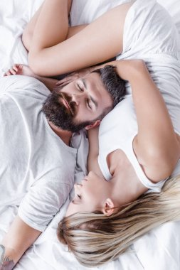 handsome man and pretty young girl lying and sleeping on white blanket