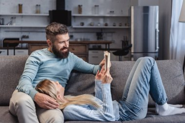 Wife holding book and lying on knees of husband