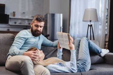 Wife reading book and lying on knees of handsome husband