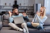 Manžel a manželka sedí, smáli se a házení popcorn v pokoji