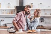 pohledný mladý pár spolu snídat v kuchyni