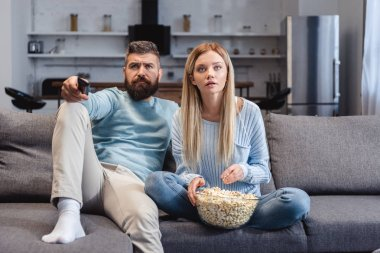 Surprised wife sitting on sofa with husband and holding popcorn
