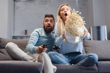 Surprised wife scattering popcorn and sitting on sofa with husband