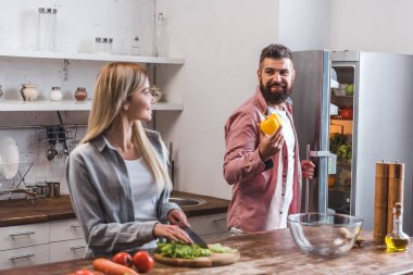 Wife cutting salad leaves and husband standing near refrigerator