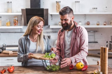 Cheerful couple adding salad leaves in bowl