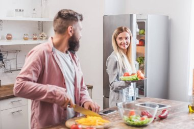 Husband cutting vegetables and wife standing near refrigerator