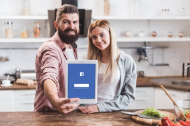 couple holding digital tablet with facebook app on screen at kitchen