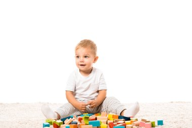 smiling toddler boy sitting on carpet and playing with multicolored wooden building blocks isolated on white