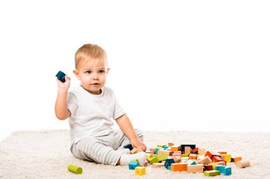 cute toddler boy sitting on carpet and playing with colored wooden building blocks isolated on white