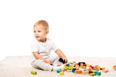 Cute toddler boy smiling and playing with wooden blocks on carpet isolated on white stock vector