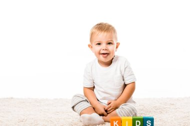 Laughing toddler boy sitting on carpet near colored cubes with letters isolated on white stock vector