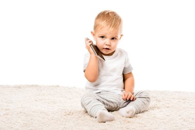 adorable toddler boy holding smartphone and sitting on carpet isolated on white