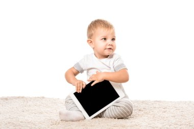 nice toddler boy sitting on carpet and holding digital tablet isolated on white