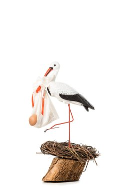 decorative stork holding baby nappy with doll and standing in wicker nest isolated on white