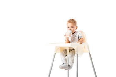 Adorable toddler boy sitting in highchair and drinking from baby bottle isolated on white stock vector