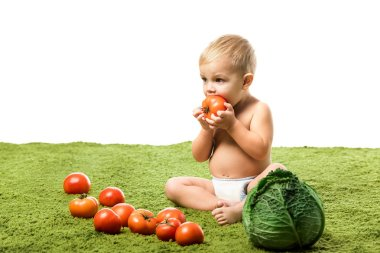 Cute toddler boy eating tomato and sitting on green carpet near with vegetables isolated on white stock vector