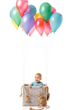 toddler boy smiling and standing in wicker basket with multicolored balloons isolated on white