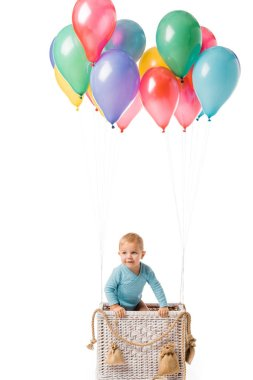Smiling toddler boy in basket with multicolored balloons isolated on white stock vector