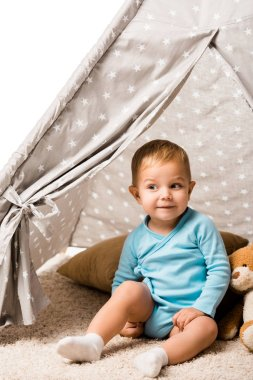 cute toddler boy smiling and sitting in baby wigwam with pillow and teddy bear isolated on white