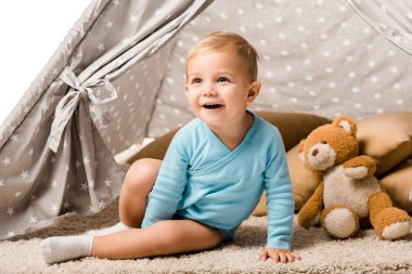 toddler boy sitting in baby wigwam with pillow and teddy bear and laughing isolated on white