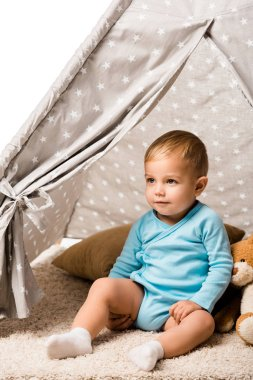 Toddler boy sitting in baby wigwam with pillow and teddy bear isolated on white stock vector