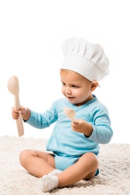 toddler boy in chefs hat sitting on carpet, holding two big wooden spoons and smiling isolated on white