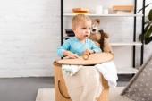 roztomilé dítě v modrou kombinézu, stojící poblíž proutěný koš prádlo v místnosti se světlem