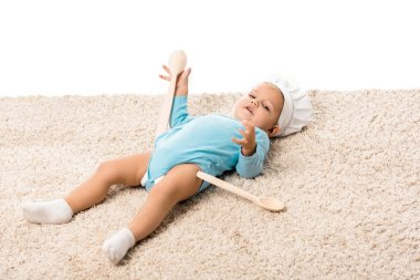 Toddler boy in chefs hat with two big wooden spoons lying on carpet and looking at camera isolated on white stock vector