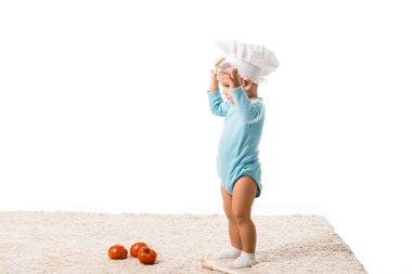 toddler boy in chefs hat standing near fresh tomatoes on carpet isolated on white