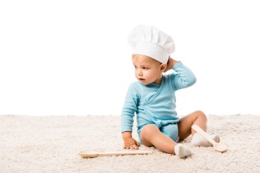 Toddler boy in chefs hat sitting on carpet near two big wooden spoons isolated on white stock vector