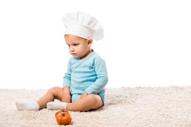 serious toddler boy in chefs hat sitting on carpet near fresh tomatoes isolated on white