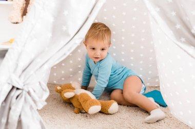 Cute toddler boy in blue bodysuit sitting on carpet in baby wigwam stock vector