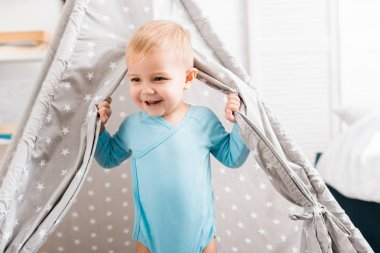 Close up view of smiling toddler boy in blue bodysuit standing in baby wigwam stock vector