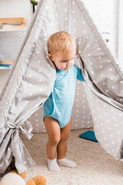 Cute toddler boy in blue bodysuit standing in grey baby wigwam on carpet stock vector