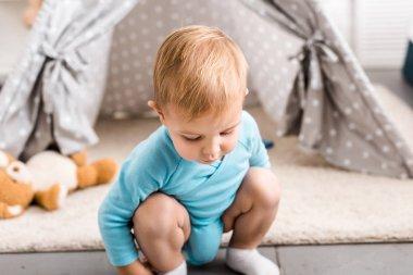 Cute toddler boy in blue bodysuit sitting on hunkers near grey wigwam stock vector
