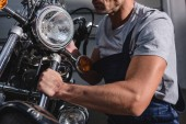 Fotografie oříznutý pohled mechanik stanovení světlometů motocyklů v garáži