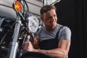 usmívající se mechanik kontrola motocyklu předního kola v garáži
