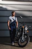 Fotografie adult mechanic in overalls standing near motorcycle in garage