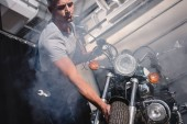 Photo guy smoking cigarette and checking motorbike front wheel in garage