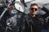 jóképű srác ül a garázsában motorkerékpárt napszemüveg