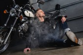 Fotografie handsome man in leather jacket resting by motorcycle in garage