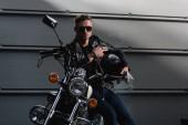fešák v černé sluneční brýle a kožená bunda na motocykl v garáži