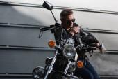 klasszikus versenyző ül a garázsában motorkerékpárt fekete napszemüveg