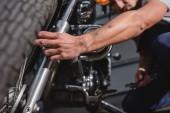 Detailní záběr na mechanické upevnění motorku předního kola v garáži