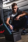 Photo mechanic sitting by toolbox on floor in garage